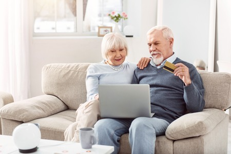 Shopping online. Grey-bearded man and short-haired woman purchasing clothes through internet while surfing internet