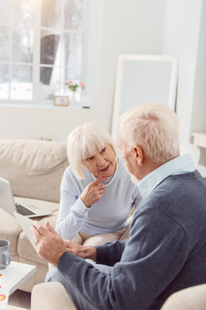 Lets discuss. Elderly happy couple sitting on the sofa while discussing the project photos