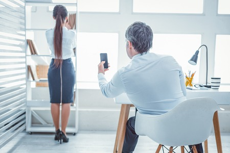 Workmate recording. Grey-haired man sitting at the desk and photographing his beautiful partner with mobile phone camera Stock Photo