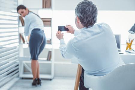 Photographier un beau partenaire. Patron méchant faisant des photos de son collègue aux cheveux longs alors qu'il était assis avec un ordinateur portable Banque d'images