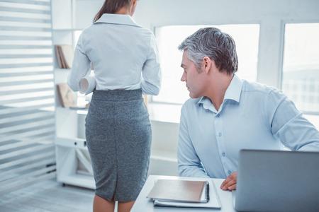 Visualisation supérieure. Homme en col blanc aux cheveux gris regardant une femme partenaire qui reste derrière sans se douter de rien Banque d'images