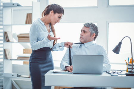 Tenir la cravate. Belle femme résolue de son collègue aux cheveux gris Banque d'images