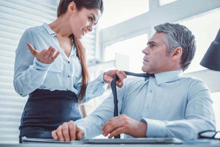 Cravate grossièrement agrippante. Belle femme grossière demandant expressivement à son collègue tout en tenant sa cravate avec sa main
