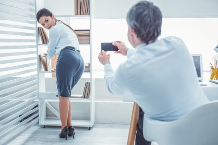 Boss making photos. Young confused woman feeling awfully because of her superior who secretly making photos