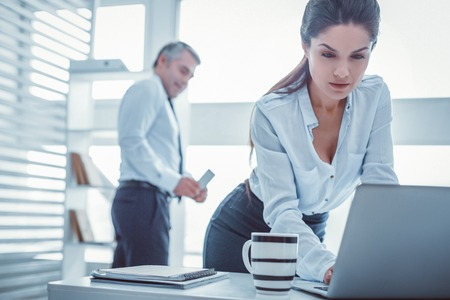 Unprofessional workmate. Long-haired beautiful woman working with laptop at office without suspecting her boss Banque d'images