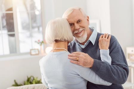 Elegant aging lady smiling while hugging her bearded husband