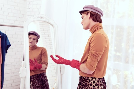 Male being happy. Attractive cross-dresser trying on bright gloves during picking and thinking about his whole look Stock Photo
