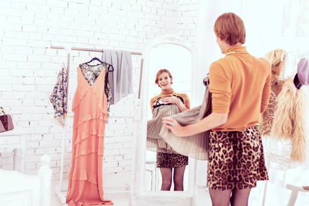 Transgender satisfied. Good-looking tall queer man attaching short grey dress choosing outfit for night