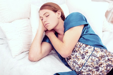 Female cloths. Ginger short-haired transgender quietly sleeping on his bed being dressed in female blue nightie
