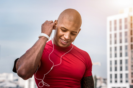 Favourite tunes. Joyful nice man wearing headphones while wanting to listen to music