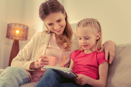 Difficult task. Pleasant cute girl asking her mother for help while doing her homework