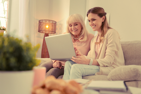 Technological progress. Cheerful aged woman smiling while learning how to use a laptop