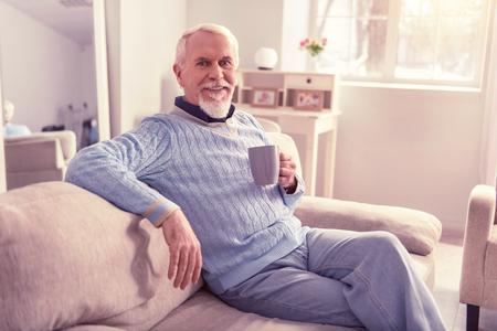 Joyful elder men. Joyful elder men wearing all blue outfits resting on his couch in well-furnished apartments Imagens