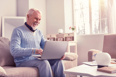 Smiling elder man. Openly smiling elder man confidently working with laptop sitting on couch at home