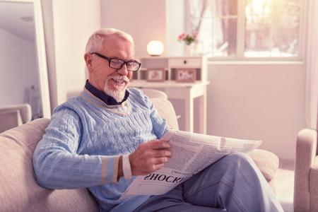 Pensioner having fun. Beaming pensioner having fun reading newspaper while chilling at home