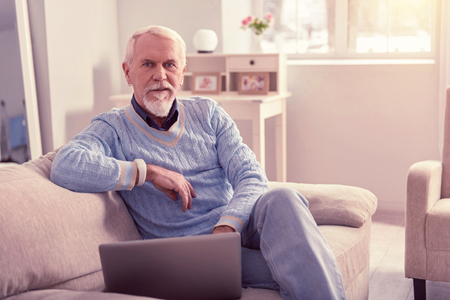 Insightful elder man. Insightful elder man wearing blue sweater and jeans having laptop nearby on sofa