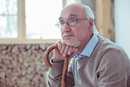 Mature person. Thoughtful male person raising eyebrows and leaning on walking stick