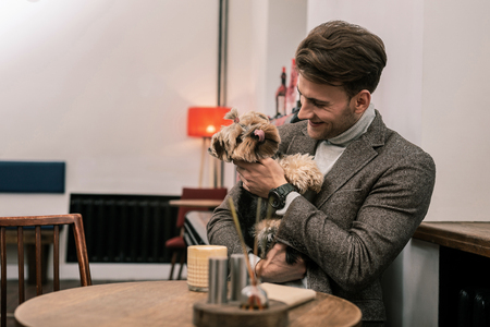 A funny dog. The man is hugging a dog while it showing its tongue