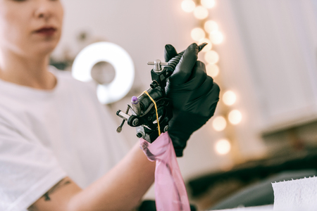 Afraid of procedure. Female tattoo master holding special machine with her hands covered in black rubber gloves