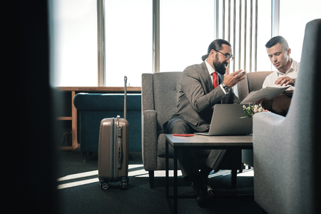 Near luggage. Two successful prosperous business partners sitting on sofa in hotel lobby near their luggage Stock Photo