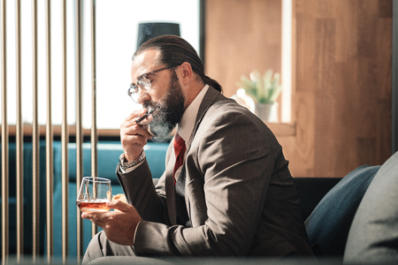 Very nervous. Bearded mature prosperous businessman smoking cigar while feeling very nervous