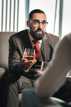 Glass of whisky. Bearded dark-haired man wearing red tie holding glass of whisky while talking to his employee Фото со стока