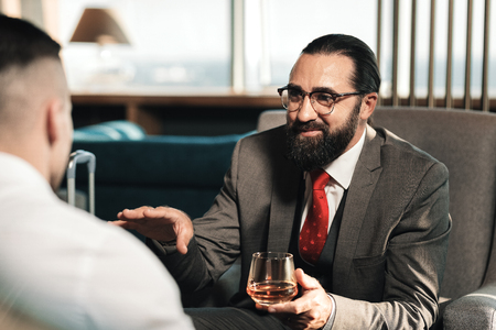 Talking to client. Bearded lawyer wearing glasses drinking whisky while talking to his client Фото со стока