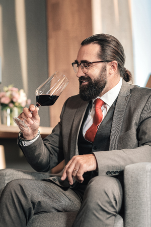 After degustation. Bearded mature businessman feeling satisfied after degustation of nice red wine
