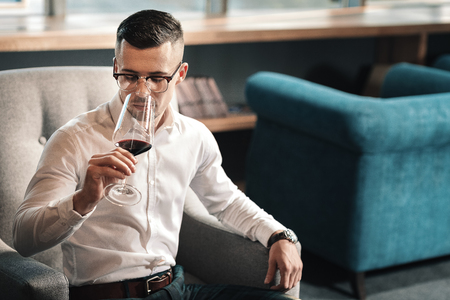 Man and wine. Handsome young man trying red wine while sitting in grey armchair after long tiring day