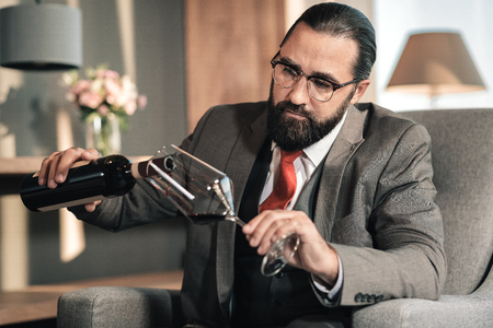 Red wine. Man wearing glasses and red tie pouring red wine into his glass after long tiring day