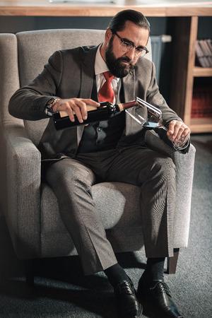 Wine after work. Dark-haired mature businessman wearing stylish costume drinking wine after work