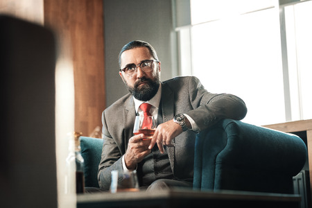 Glass of cognac. Dark-haired bearded mature lawyer wearing glasses drinking glass of cognac