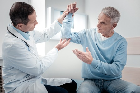 Take it higher. Serious physician looking at his patient while examining elbow