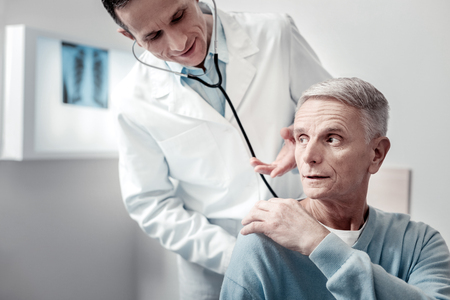 Mature visitor. Attentive physician bowing head while communicating with patient Фото со стока