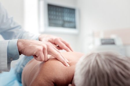 Medical massage. Professional physician examining mature patient, giving results Stock Photo