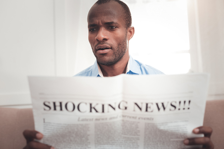 Shocking news. Pleasant surprised man holding a newspaper while reading shocking news Banque d'images - 115820679