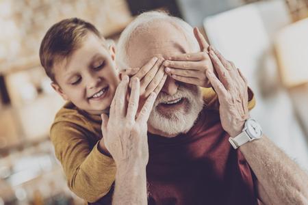I got you. Joyful kid keeping smile on face while covering eyes