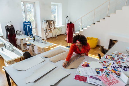 Design cloths. Concentrated curly African American designer using measuring tape for cutting paper layout
