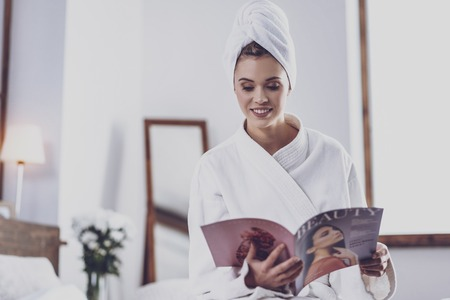 Fashion magazine. Young gorgeous positive woman having a rest after SPA procedures while holding magazine and reading interesting article