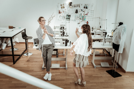 Time to dance. Tall handsome dressmaker feeling wonderful with the beautiful model wearing a beige dress