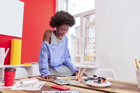 Working hard. Young stylish beautiful artist wearing striped dress and blue shirt working hard Stockfoto