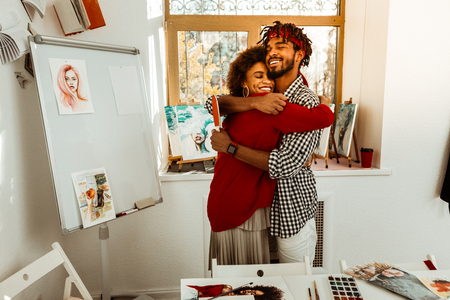 Loving man. Loving handsome bearded man hugging his beautiful curly dark-haired girlfriend Banco de Imagens