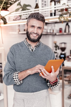Digital technology. Delighted handsome man holding a tablet while standing in front of the counter Imagens