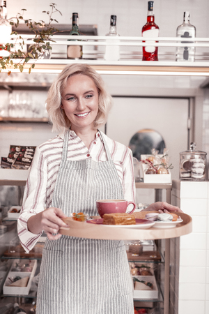 In the coffee shop. Delighted cheerful waitress smiling while holding a tray with breakfast