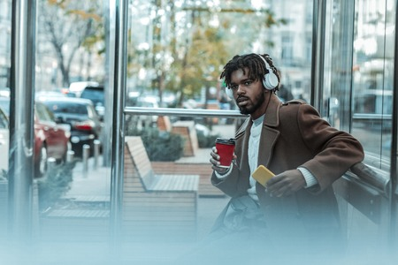 So concentrated. Serious bearded man wearing headphones and drinking coffee 免版税图像