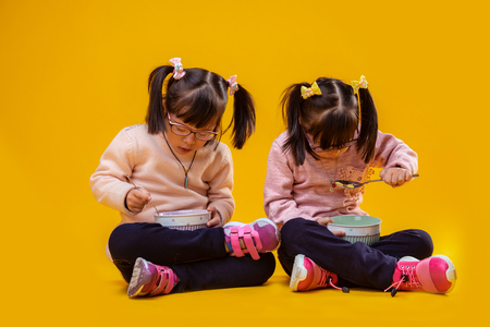 Happy and positive. Attentive pretty little sisters sitting on bare floor and eating cereals from deep bowls Stockfoto