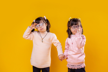 Staying together. Nice little children with down syndrome being photo models and staying in front of yellow background 免版税图像