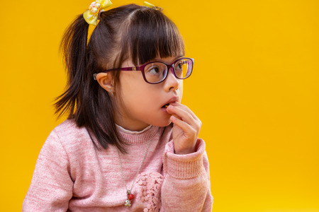 Unusual face features. Thoughtful dark-haired child with abnormality eating snacks while being dressed in pink warm sweater Stockfoto