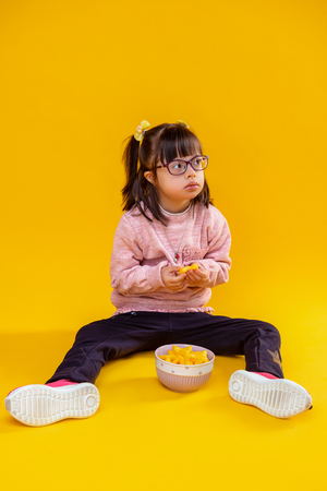 On orange background. Curious serious little lady sitting on floor against bowl full of unhealthy snacks