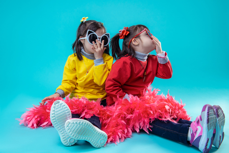 Being carefree together. Two happy girls sitting on studio floor while wearing glasses and covering legs with red festive boa